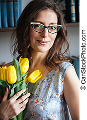 Smiling woman writer sitting indoors while holding tulips. -...