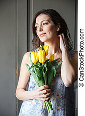 Happy woman writer sitting indoors while holding tulips. -...
