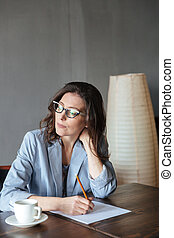 Thoughtful woman writer sitting indoors - Image of...