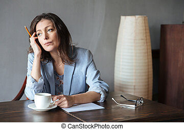 Thinking serious woman writer sitting indoors - Image of...