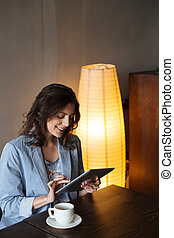 Happy woman using tablet computer.