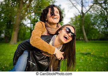 Two cute young women cheerfully spend time in the spring...