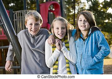 Portrait of children at park - Three children (10-11 years)...