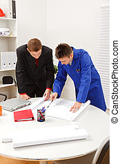 Boss and employee surveying plans - Young boss and employee...