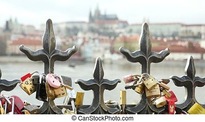 Forged metal fence covered with love padlocks on a river bank in Prague
