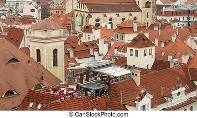 The old red tile roofs of medieval buildings and towers  in Prague in autumn