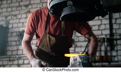 The blacksmith handles the item is removed from the fire,...