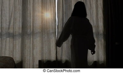 A young, beautiful woman in a white coat comes to the window, opens the curtains and looks at him. Sunny morning
