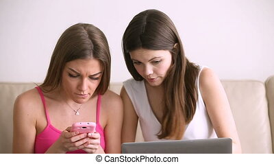 Two happy young women shopping via laptop and mobile apps -...