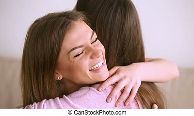 Two pretty women embracing, close friends hugging, laughing having fun