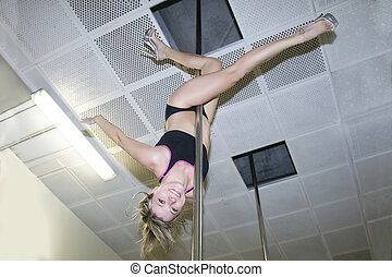 Young pole dance woman upside down in dance hall