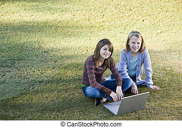 Young girls using laptop on grass - Two young friends 10 and...