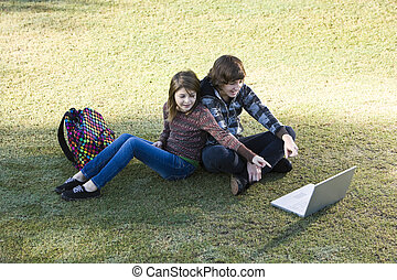 Children using laptop in park - Boy and girl sitting on...