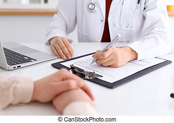 Close up of a female doctor filling up  an application form while consulting patient