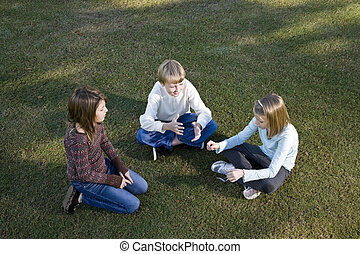 Children sitting in a circle on grass talking - Three...