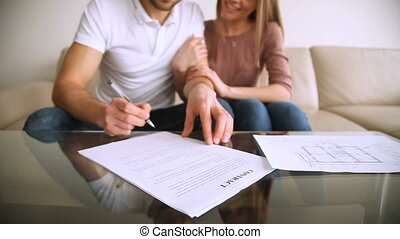 Happy young couple signing contract agreement and hugging,...