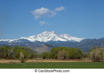 Snow capped Longs Peak and Mt Meeker on a spring or summer...