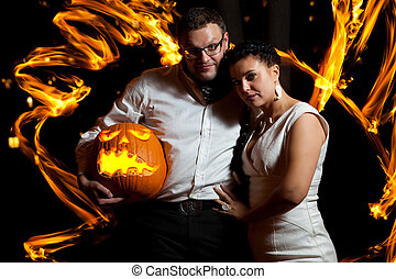 Pretty couple with the pumpkin surrounded by fire flames