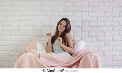 girl stretches before bedtime - charming young girl sits in...