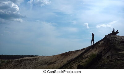 a young athletic woman walks on top of the Hill