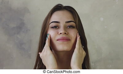 woman moisturizes face cream - beauty young woman...