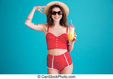 Happy young lady with cocktail looking at camera