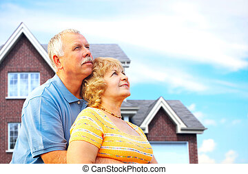 Elderly couple near their home Real estate and insurance...