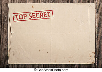Open top secret envelope on table - Open yellow envelope...