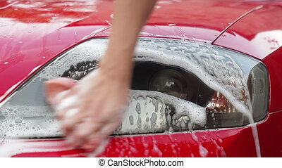 Girl rubs car headlamp with soap and sponge