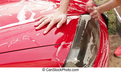 girl washes a headlamp of red car outdoors with sponge and...