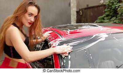 woman washes a red car