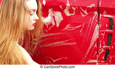 young girl washes a red car