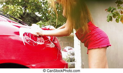 girl washes a red car - young sexual lady washes a red car...