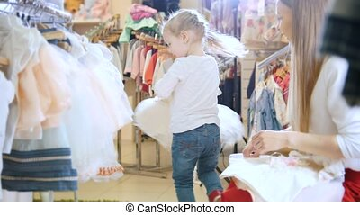Mother and daughter in store of children clothing, telephoto