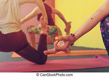 Three females practicing yoga in class, closeup