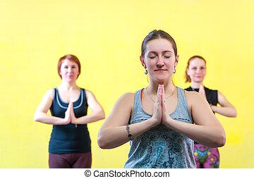 Portrait of three caucasian women practicing yoga