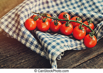 Sprig of fresh red cherry tomatoes on a wooden background in...