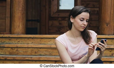 Pretty girl checking information on her mobile outdoors
