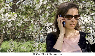 Young woman talking on smartphone in blooming trees