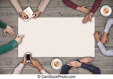 Teamwork and cooperation concept - top view of six people drawing or writing on a large white blank sheet of paper.