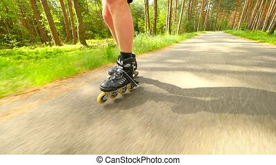 Shuffle inline skating on way in pine forest. Mans legs...