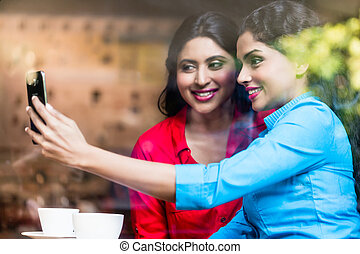 Customers in Indian cafe taking selfie, view through shop...