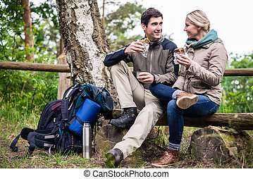 Couple on hike taking rest under tree - Loving couple, woman...