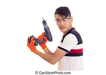 Young man with gloves and glasses holding electric screwdriver