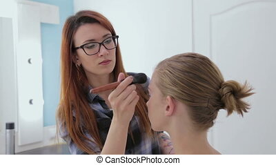 Professional make-up artist applying powder to girl face in...