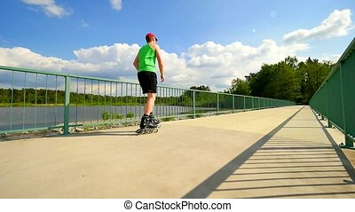 Rear view to inline skater in green singletand black pants...
