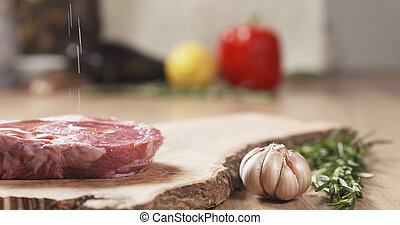 olive oil pour onto raw rib eye steak on board