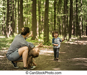 Mother with young daughters walk in the woods - a young...