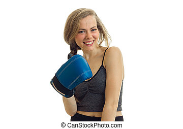 Portrait of a smiling young blond chic that stands in front of the camera in boxing gloves