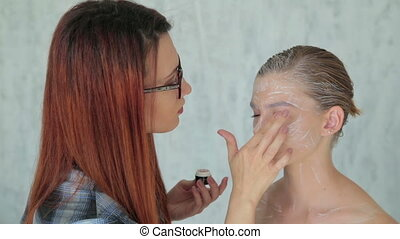 Professional make-up artist making face art in white room -...